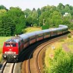 Roter Zug mit Wagons fährt durch grüne Landschaft