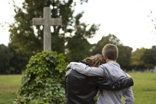 Zwei Jugendliche stehen vor einem Grab