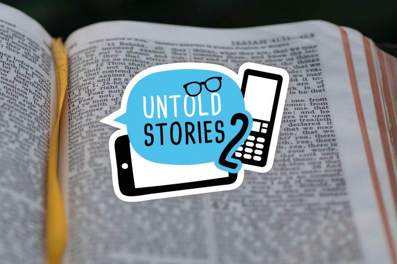 """Bild mit Untold Stories Logo (Grafik mit Sprechblase mit dem Schriftzug """"Untold Stories 2"""" und zwei Smartphones) über aufgeschlagener Bibel."""