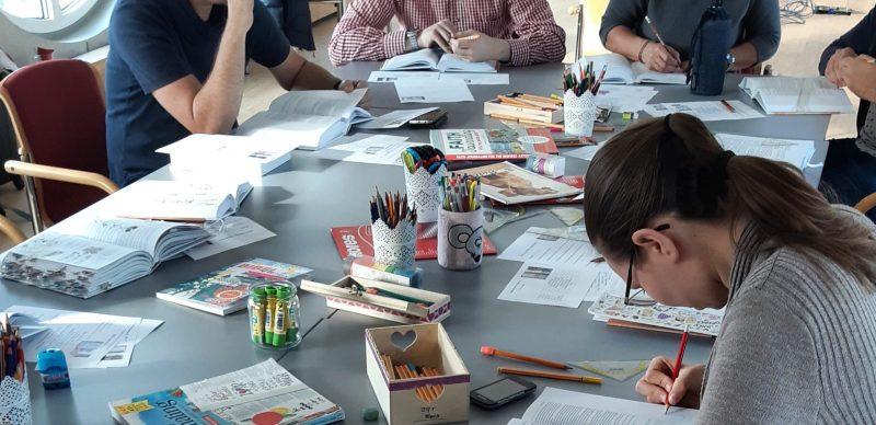 Foto: junge Leute sitzen an einem Tisch, der voll mit Stiften und Büchern bedeckt ist.