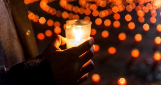 Foto: eine Hand hält ein brennendes Teelicht, dahinter verschwommen, brennende Kerzen