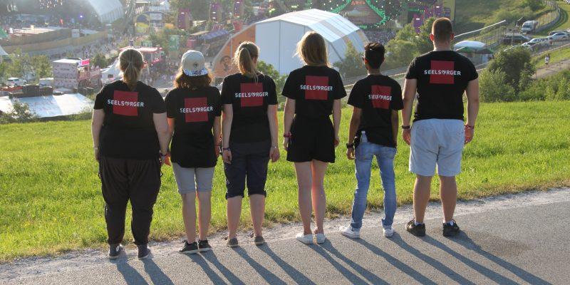 """Foto: 6 Personen stehen mit dem Rücken zur Kamera. Sie tragen alle ein T-Shirt auf dem das Wort """"Seelsorger"""" aufgedruckt ist. Im Hintergrund sieht man ein Festivalgelände."""